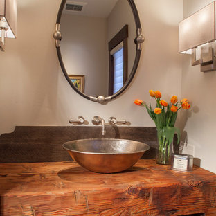 Powder room - rustic powder room idea in Denver with white walls, a vessel sink and wood countertops