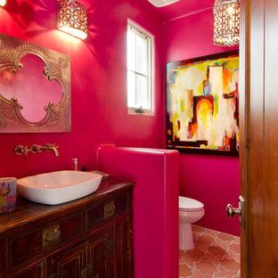 Foto di un bagno di servizio american style di medie dimensioni con lavabo a bacinella, consolle stile comò, ante in legno bruno, WC monopezzo, pareti rosa e pavimento in terracotta