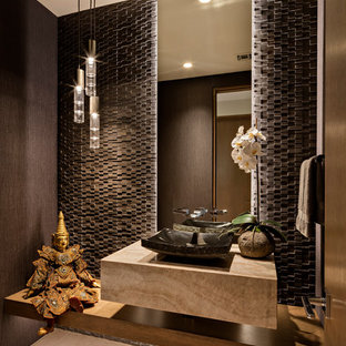 Modelo de aseo de estilo americano, grande, con suelo de baldosas de porcelana, encimera de ónix, suelo beige, baldosas y/o azulejos negros, paredes negras, lavabo sobreencimera y encimeras beige