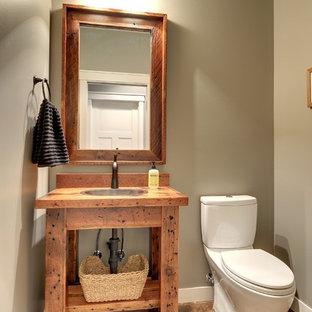 Пример оригинального дизайна: туалет в стиле кантри с раздельным унитазом, коричневыми стенами, паркетным полом среднего тона, накладной раковиной, столешницей из дерева, коричневым полом и коричневой столешницей
