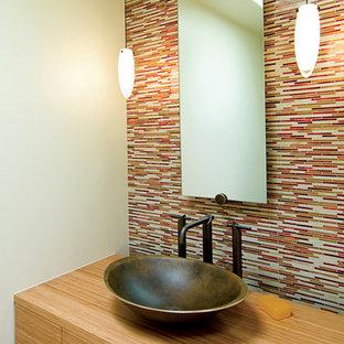 Неиссякаемый источник вдохновения для домашнего уюта: маленький туалет в современном стиле с настольной раковиной, плоскими фасадами, светлыми деревянными фасадами, столешницей из дерева, разноцветной плиткой, бежевыми стенами, удлиненной плиткой и коричневой столешницей