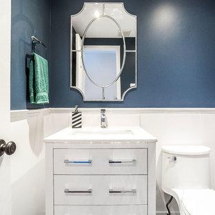 На фото: маленький туалет в стиле современная классика с фасадами островного типа, белыми фасадами, унитазом-моноблоком, синими стенами, мраморным полом, врезной раковиной, столешницей из кварцита, черным полом и белой столешницей с