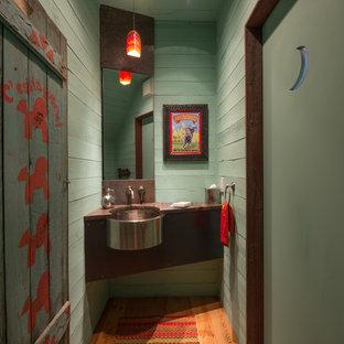 Immagine di un bagno di servizio rustico con lavabo sottopiano, pareti verdi e pavimento in legno massello medio