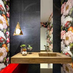 Esempio di un piccolo bagno di servizio contemporaneo con ante lisce, ante rosse, piastrelle nere, piastrelle in gres porcellanato, pareti multicolore, lavabo integrato e top marrone