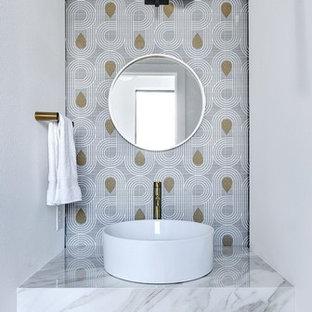 Réalisation de WC et toilettes nordiques avec un mur multicolore, une vasque, un plan de toilette en marbre et un sol blanc.