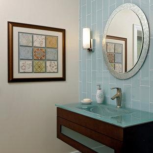 Exemple d'un WC et toilettes tendance de taille moyenne avec un lavabo intégré, un placard à porte plane, des portes de placard en bois sombre, un plan de toilette en verre, un carrelage bleu, un carrelage en pâte de verre, un mur blanc, un sol en travertin, un sol beige et un plan de toilette turquoise.