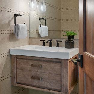 Kleine Urige Gästetoilette mit flächenbündigen Schrankfronten, hellbraunen Holzschränken, Wandtoilette mit Spülkasten, beiger Wandfarbe, Schieferboden, integriertem Waschbecken, Mineralwerkstoff-Waschtisch, grauem Boden, weißer Waschtischplatte, schwebendem Waschtisch und Tapetenwänden in Denver