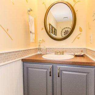 Inspiration för mellanstora klassiska toaletter, med ett nedsänkt handfat, luckor med upphöjd panel, grå skåp, laminatbänkskiva, en toalettstol med hel cisternkåpa, beige kakel, keramikplattor, gula väggar och mellanmörkt trägolv