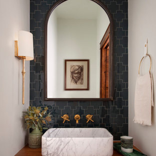 Example of a mid-sized tuscan black tile and porcelain tile powder room design in Austin with a drop-in sink, white walls, wood countertops, brown countertops and a floating vanity