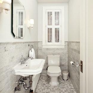 ワシントンD.C.の小さいヴィクトリアン調のおしゃれなトイレ・洗面所 (壁付け型シンク、分離型トイレ、モノトーンのタイル、グレーのタイル、白い壁、大理石の床、大理石タイル) の写真