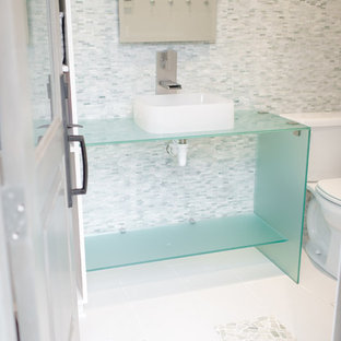Design ideas for a medium sized traditional cloakroom in Dallas with open cabinets, a one-piece toilet, multi-coloured tiles, mosaic tiles, mosaic tile flooring, a vessel sink, glass worktops, blue cabinets, white walls, white floors and blue worktops.