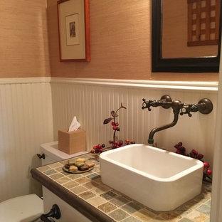 На фото: туалеты в стиле кантри с белыми фасадами, разноцветной плиткой, каменной плиткой, коричневыми стенами, настольной раковиной, столешницей из плитки и раздельным унитазом