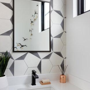 Aménagement d'un petit WC et toilettes contemporain avec un placard à porte plane, des portes de placard marrons, un WC à poser, un carrelage noir et blanc, des carreaux de béton, un mur blanc, un sol en carreaux de ciment, un lavabo encastré, un plan de toilette en quartz modifié et un plan de toilette blanc.