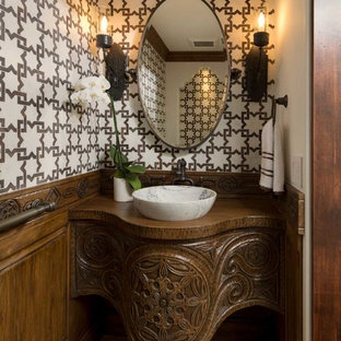 Inspiration for a mediterranean brown floor powder room remodel in San Diego with medium tone wood cabinets, multicolored walls, a vessel sink, wood countertops and brown countertops