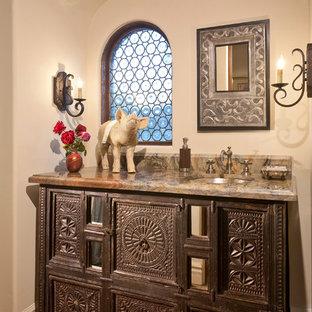 На фото: туалеты в средиземноморском стиле с фасадами островного типа, коричневыми фасадами, бежевыми стенами, полом из терракотовой плитки, врезной раковиной и оранжевым полом