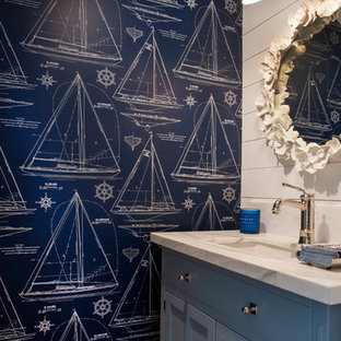 Inspiration for a small beach style cloakroom in San Diego with shaker cabinets, blue cabinets, a two-piece toilet, white tiles, blue walls, light hardwood flooring, a submerged sink, engineered stone worktops, grey floors and multi-coloured worktops.