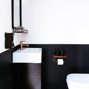 Идея дизайна: маленький туалет в современном стиле с унитазом-моноблоком, черно-белой плиткой, цементной плиткой, черными стенами, полом из цементной плитки и консольной раковиной