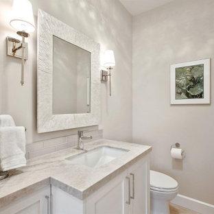 Réalisation d'un WC et toilettes avec un placard à porte shaker, des portes de placard blanches, un WC à poser, un carrelage en pâte de verre, un mur beige, un sol en travertin, un lavabo encastré, un plan de toilette en quartz, un sol beige et meuble-lavabo encastré.
