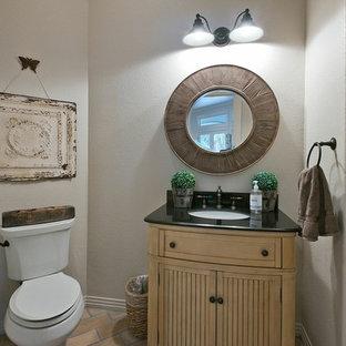 Cette image montre un petit WC et toilettes traditionnel avec un lavabo encastré, un placard en trompe-l'oeil, des portes de placard en bois clair, un plan de toilette en granite, un WC séparé, un mur beige, un sol en brique et un sol beige.