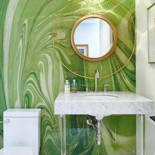 Réalisation d'un WC et toilettes design avec un mur vert, un lavabo encastré et un plan de toilette en marbre.