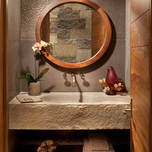 Réalisation d'un WC et toilettes chalet avec un lavabo intégré, un mur gris et un plan de toilette gris.