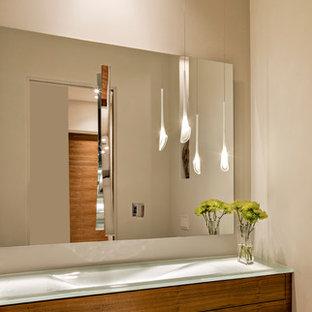 Réalisation d'un grand WC et toilettes minimaliste avec un placard à porte plane, des portes de placard en bois brun, un WC à poser, des plaques de verre, un mur beige, un sol en carrelage de céramique, un lavabo posé et un plan de toilette en verre.
