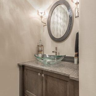 Cette image montre un WC et toilettes traditionnel avec des portes de placard en bois vieilli, un mur beige, un sol en bois brun, une vasque et un plan de toilette en terrazzo.
