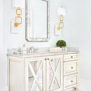 Aménagement d'un WC et toilettes contemporain de taille moyenne avec un placard à porte vitrée, des portes de placard blanches, un mur bleu, un sol en marbre, un lavabo encastré, un plan de toilette en granite et un sol blanc.