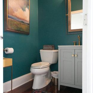Foto di un piccolo bagno di servizio contemporaneo con ante in stile shaker, ante grigie, pareti verdi, pavimento in legno massello medio, pavimento marrone e top bianco
