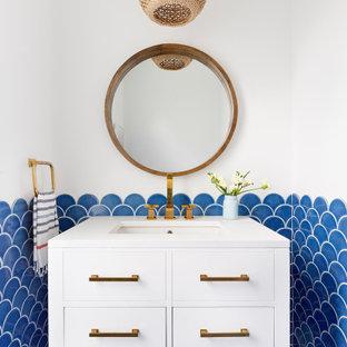 Imagen de aseo costero con armarios con paneles lisos, puertas de armario blancas, baldosas y/o azulejos azules, paredes blancas, lavabo bajoencimera, suelo azul y encimeras blancas