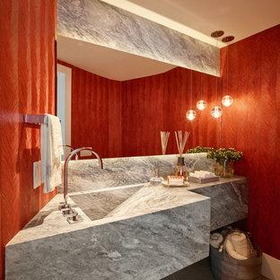 Idee per un bagno di servizio design di medie dimensioni con lavabo integrato, top in marmo, WC monopezzo, piastrelle grigie, lastra di pietra, pareti rosse e pavimento in gres porcellanato