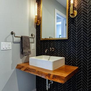 Modelo de aseo contemporáneo, de tamaño medio, con baldosas y/o azulejos negros, lavabo sobreencimera, encimera de madera, suelo gris, paredes grises, encimeras marrones, baldosas y/o azulejos de porcelana y suelo de baldosas de porcelana