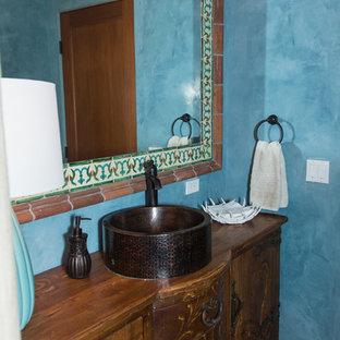 Пример оригинального дизайна: туалет среднего размера в средиземноморском стиле с фасадами островного типа, фасадами цвета дерева среднего тона, синими стенами, полом из терракотовой плитки, настольной раковиной, столешницей из дерева и коричневым полом