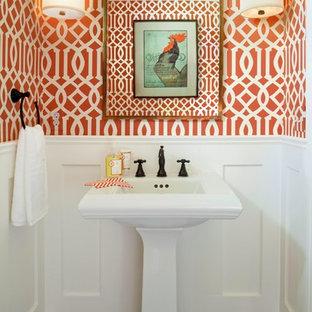 デンバーの小さいコンテンポラリースタイルのおしゃれなトイレ・洗面所 (ペデスタルシンク、オレンジの壁、濃色無垢フローリング、分離型トイレ、茶色い床) の写真