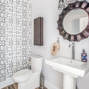 Идея дизайна: маленький туалет в стиле кантри с белыми стенами, полом из ламината, раковиной с пьедесталом и раздельным унитазом