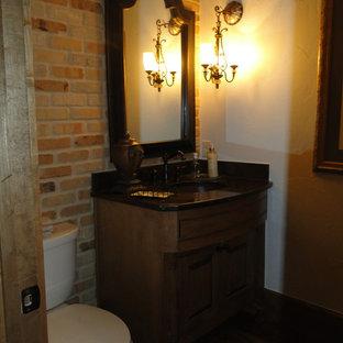 Foto de aseo de estilo americano, pequeño, con puertas de armario de madera oscura, sanitario de dos piezas, paredes beige, suelo de madera oscura, lavabo bajoencimera y encimera de acrílico
