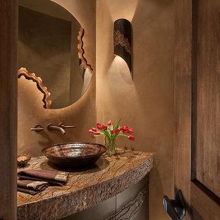 Идея дизайна: туалет среднего размера в стиле фьюжн с настольной раковиной, фасадами островного типа, столешницей из гранита, бежевыми стенами, полом из галечной плитки и темными деревянными фасадами