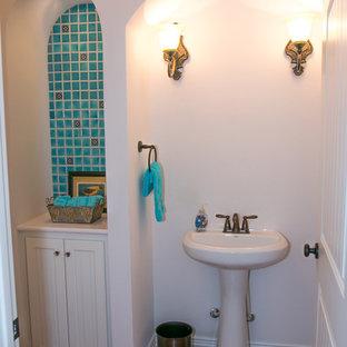 На фото: туалет среднего размера в стиле фьюжн с фасадами с утопленной филенкой, белыми фасадами, раздельным унитазом, терракотовой плиткой, белыми стенами, полом из терракотовой плитки, раковиной с пьедесталом, столешницей из искусственного камня, оранжевым полом и белой столешницей с