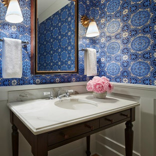 Inspiration for a mid-sized traditional powder room in Minneapolis with an undermount sink, furniture-like cabinets, dark wood cabinets, marble benchtops, blue walls, medium hardwood floors and white benchtops.