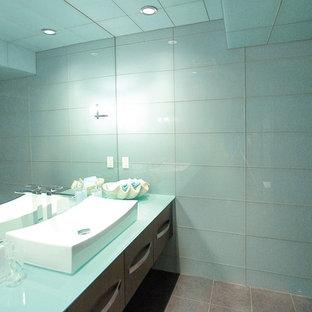 На фото: маленький туалет в современном стиле с настольной раковиной, плоскими фасадами, темными деревянными фасадами, унитазом-моноблоком, серой плиткой, керамогранитной плиткой, синими стенами, полом из керамической плитки и стеклянной столешницей
