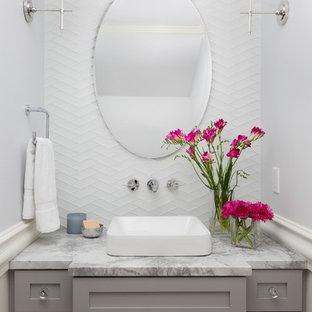 Klassische Gästetoilette mit Schrankfronten im Shaker-Stil, grauen Schränken, weißen Fliesen, Glasfliesen, grauer Wandfarbe, Aufsatzwaschbecken, Marmor-Waschbecken/Waschtisch und grauer Waschtischplatte