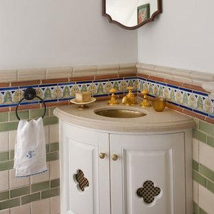 サンディエゴの小さい地中海スタイルのおしゃれなトイレ・洗面所 (アンダーカウンター洗面器、白いキャビネット、トラバーチンの洗面台、白い壁、テラコッタタイルの床) の写真