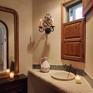 Idee per un piccolo bagno di servizio mediterraneo con ante in legno bruno, piastrelle a mosaico, pareti beige, pavimento in terracotta, lavabo da incasso e top piastrellato