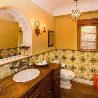 Пример оригинального дизайна: туалет в средиземноморском стиле с темными деревянными фасадами, раздельным унитазом, разноцветной плиткой, желтыми стенами и темным паркетным полом