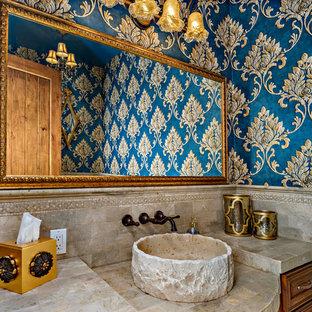 Пример оригинального дизайна: туалет среднего размера в средиземноморском стиле с фасадами с выступающей филенкой, коричневыми фасадами, унитазом-моноблоком, бежевой плиткой, плиткой из травертина, синими стенами, полом из травертина, настольной раковиной, столешницей из травертина, бежевым полом и бежевой столешницей