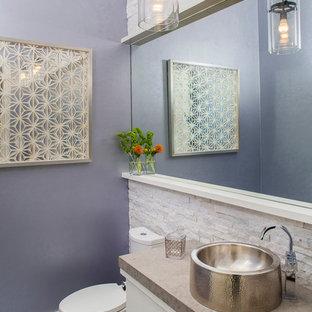 Réalisation d'un grand WC et toilettes design avec un placard à porte plane, des portes de placard blanches, un plan de toilette en calcaire, un carrelage blanc, un WC à poser, une vasque, un mur violet, un sol en marbre, du carrelage en pierre calcaire et un plan de toilette beige.