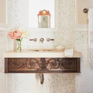 Cette photo montre un petit WC et toilettes méditerranéen avec un placard sans porte, des portes de placard en bois vieilli, un WC à poser, un carrelage blanc, carrelage en mosaïque, un mur beige, un sol en bois foncé, un lavabo encastré, un plan de toilette en calcaire, un sol marron et un plan de toilette beige.
