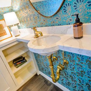Immagine di un piccolo bagno di servizio mediterraneo con lavabo sottopiano, ante bianche, top in marmo, WC a due pezzi, pavimento in legno massello medio e pareti blu
