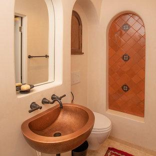 Пример оригинального дизайна: туалет в средиземноморском стиле с инсталляцией, разноцветной плиткой, оранжевой плиткой, бежевыми стенами, подвесной раковиной и бежевым полом