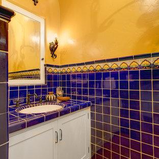 На фото: туалет среднего размера в средиземноморском стиле с фасадами в стиле шейкер, белыми фасадами, синей плиткой, разноцветной плиткой, керамической плиткой, желтыми стенами, полом из терракотовой плитки, врезной раковиной, столешницей из плитки, красным полом и синей столешницей